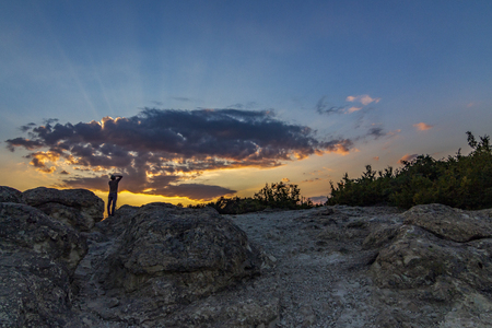 Rear view of unrecognizable male photographer taking pictures of the sunset over the Stone Mushrooms near Beli Plast village, Kardzhali Municipality, Bulgaria 写真素材