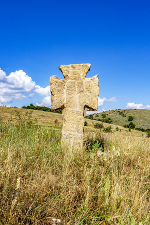 Ancient stone cross on a hill near the village of Malo Malovo, Dragoman Municipality, Sofia Province, Western Bulgaria on a sunny summer day Standard-Bild - 119629268