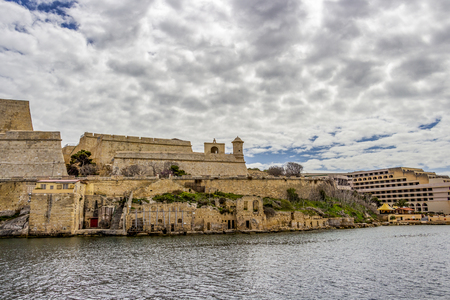 Valletta fortification next to Grand Hotel Excelsior under overcast March sky, at Valletta, Malta