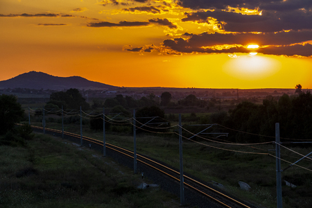 Beautiful summer sunset over sunlit empty railway tracks and an asphalt road near Krum, Southern Bulgaria, elevated view from a bridge 写真素材