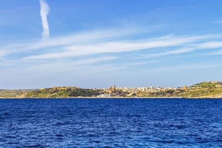 Deep blue Mediterranean Sea view of the town of Mgarr in Gozo, Malta, distant urban skyline Stok Fotoğraf