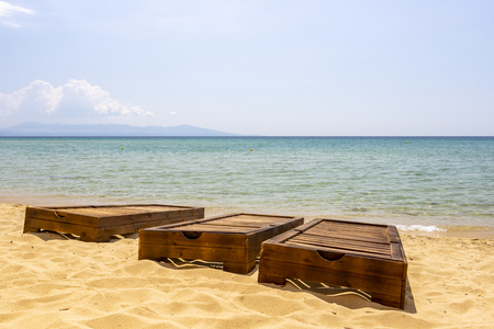 Three empty wooden sunbeds without sunbed pad cushions at Ammolofoi Beach, Kavala Region, Northern Greece Stock Photo