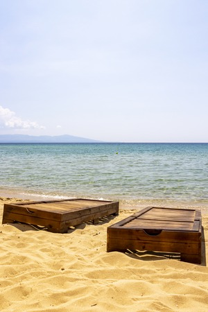 Two empty wooden sunbeds without sunbed pad cushions at Ammolofoi Beach, Kavala Region, Northern Greece Stock Photo
