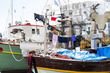 KAVALA, GREECE - JULY 20, 2018: Fishing boats at the Port of Kavala, Eastern Macedonia, Northern Greece with clothes hanging on clotheslines