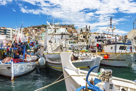 KAVALA, GREECE - JULY 20, 2018: Fishing boats at the Port of Kavala, Eastern Macedonia, Northern Greece, the old town in the background Editöryel