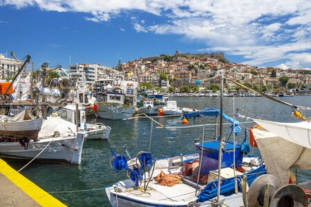 KAVALA, GREECE - JULY 20, 2018: Fishing boats at the Port of Kavala, Eastern Macedonia, Northern Greece, view of the old town in the background