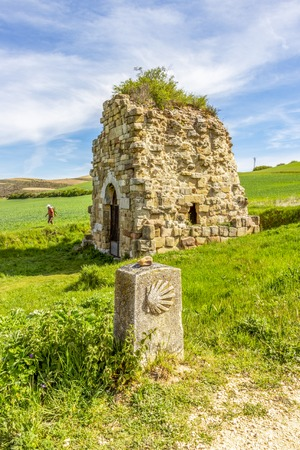 Monastery of San Felices de Oca ruins, Province of Burgos, Castilla y Leon, Spain with a Way of St. James stone scallop shell marker and a pilgrim Stock Photo
