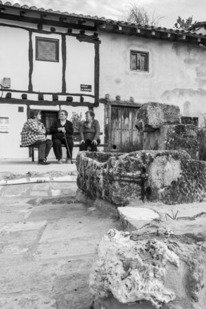BARRIOS DE COLINA, SPAIN - MAY 15, 2017: Three local women on a bench behind the old water fountain, on the Way of St. James, black and white photography