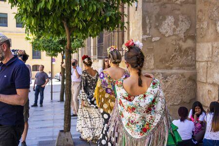 CORDOBA, SPAIN - MAY 30, 2019: Rear view of beautiful dressed female participants at Feria de Cordoba, Feria de Nuestra Senora de la Salud or Cordoba Fair Editorial