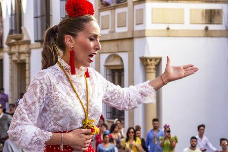 CORDOBA, SPAIN - MAY 30, 2019: Female flamenco singer sings in front of the Mosque-Cathedral at Feria de Cordoba, Feria de Nuestra Senora de la Salud or Cordoba Fair Editorial