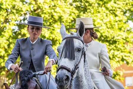 CORDOBA, SPAIN - MAY 30, 2019: Two female horse riders at Feria de Cordoba, Feria de Nuestra Senora de la Salud or Cordoba Fair