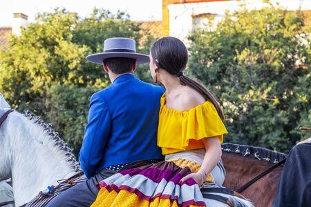 CORDOBA, SPAIN - MAY 30, 2019: A male and a female participants at Feria de Cordoba, Feria de Nuestra Senora de la Salud or Cordoba Fair on a horse, rear view