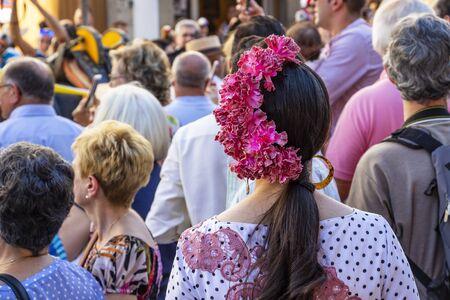 CORDOBA, SPAIN - MAY 30, 2019: Rear view of a beautiful dressed female participant at Feria de Cordoba, Feria de Nuestra Senora de la Salud or Cordoba Fair