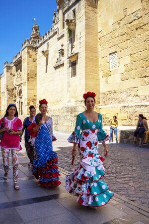 CORDOBA, SPAIN - MAY 30, 2019: Beautiful smiling dressed female participants at Feria de Cordoba, Feria de Nuestra Senora de la Salud or Cordoba Fair in front of the Mosque-Cathedral