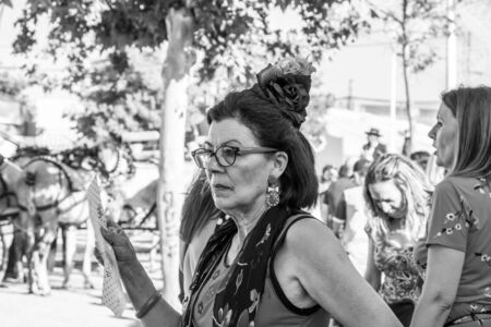 CORDOBA, SPAIN - MAY 30, 2019: Close portrait of a senior dressed female participant at Feria de Cordoba, Feria de Nuestra Senora de la Salud or Cordoba Fair with a hand fan Editorial