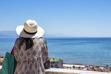 Rückansicht eines nicht identifizierten weiblichen Touristen am Aussichtsturm des Parque de la Bateria, Torremolinos, Provinz Malaga, Andalusien, Spanien mit Blick auf das Meer?
