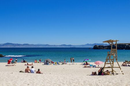 TARIFA, SPAIN - MAY 27, 2019: Sunbathing tourists at Playa Chica or Chica beach in Tarifa, Province of Cadiz, Andalusia Spain