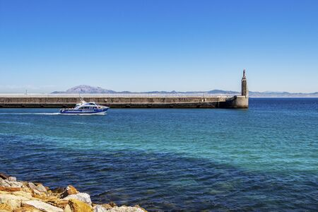 TARIFA, SPAIN - MAY 27, 2019: View of Punta del Santo with a cruise boat from a Tarifa Port breakwater, the Morocco Mountains across the Straits of Gibraltar in the distance
