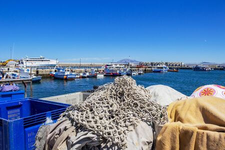 TARIFA, SPAIN - MAY 27, 2019: Port of Tarifa with fishing boats and the Virtu Ferries catamaran Maria Dolores, fishing tackle in the foreground 報道画像