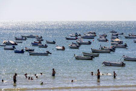 CADIZ, SPAIN - MAY 28, 2019: Playa la Caleta or La Caleta Beach with swimming tourists and boats, shimmering water surface 報道画像