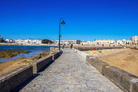 CADIZ, SPAIN - MAY 28, 2019: Causeway to the Castle of San Sebastian, view of Cadiz and Playa la Caleta or La Caleta Beach in the background 報道画像