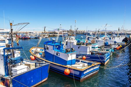 TARIFA, SPAIN - MAY 27, 2019: Port of Tarifa with fishing boats, Punta del Santo in the distance