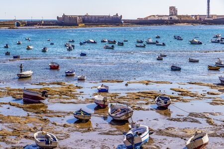 CADIZ, SPAIN - MAY 28, 2019: Playa la Caleta or La Caleta Beach low-tide shoreline with boats, view of the Castle of San Sebastian with causeway 報道画像