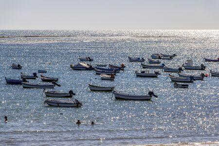 CADIZ, SPAIN - MAY 28, 2019: Playa la Caleta or La Caleta Beach shimmering water surface with boats