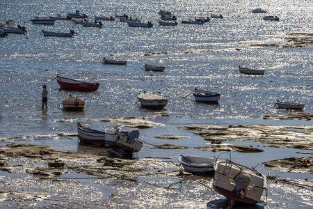 CADIZ, SPAIN - MAY 28, 2019: Playa la Caleta or La Caleta Beach shimmering water surface and low-tide shoreline with boats
