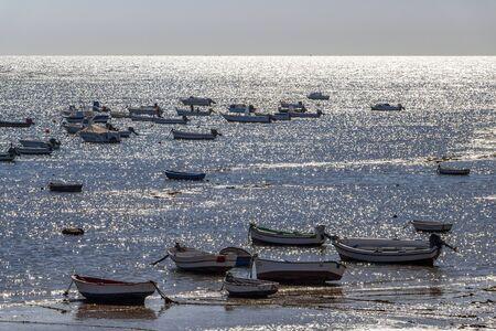 CADIZ, SPAIN - MAY 28, 2019: Playa la Caleta or La Caleta Beach shimmering water surface with fishing boats