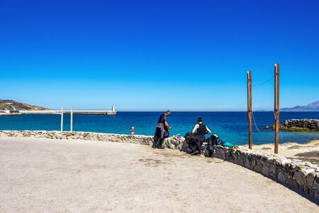 TARIFA, SPAIN - MAY 27, 2019: Two male scuba divers at the causeway to Isla de las Palomas, the southernmost point of continental Europe in Andalusia, Spain