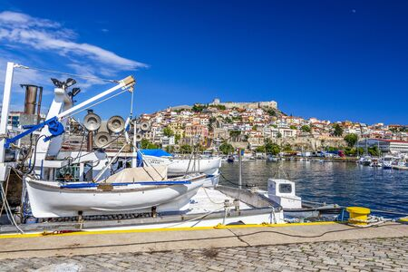 KAVALA, GREECE - JULY 20, 2018: Fishing boats at the Port of Kavala, the old town with the Byzantine fortress in the background Editöryel