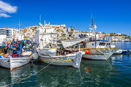 KAVALA, GREECE - JULY 20, 2018: Fishing boats at the Port of Kavala, Eastern Macedonia, Northern Greece, the old town with the Byzantine fortress in the background