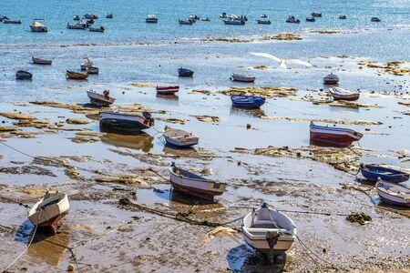 CADIZ, SPAIN - MAY 28, 2019: Playa la Caleta or La Caleta Beach low-tide shoreline with fishing boats in Cadiz, Province of Cadiz, Andalusia, Spain 報道画像