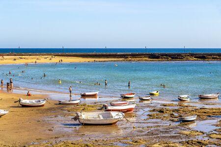 CADIZ, SPAIN - MAY 28, 2019: Playa la Caleta or La Caleta Beach low-tide shoreline with boats, view of the Castle of San Sebastian causeway