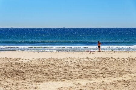 TARIFA, SPAIN - MAY 27, 2019: A couple at the empty Playa de los Lances or Los Lances Beach, silhouette of a fishing boat in the distance