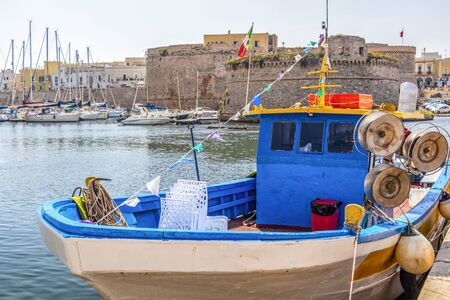 GALLIPOLI, ITALY - AUGUST 30, 2018: Fishing boat at the Port of Gallipoli, Province of Lecce, Apulia, Italy, the Castle of Gallipoli in the background