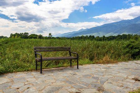 Old weathered bench at Lake Kerkini, Greece under overcast July sky Stockfoto