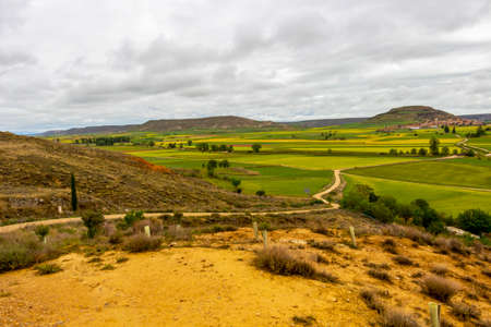 Beautiful landscape on the Way of St. James, Camino de Santiago in Castile and Leon, Spain under overcast May sky, distant view of Castrojeriz in the background