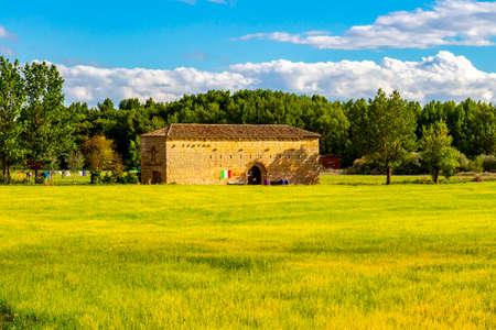 Scenic May view of the Hermitage of San Nicolas de Puente Fitero with pilgrims on the Way of St. James, Camino de Santiago. Itero del Castillo, Castile and Leon, Spain