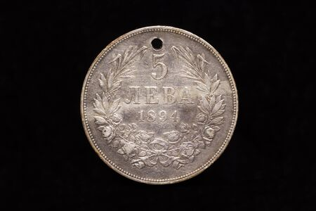 Old Bulgarian silver 5 leva coin from 1894 with a hole, reverse. Isolated on black background