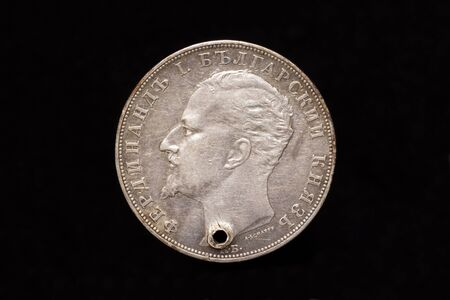 Old Bulgarian silver 5 leva coin from 1894 with a hole, obverse showing Ferdinand I. Bulgarian Prince. Isolated on black background
