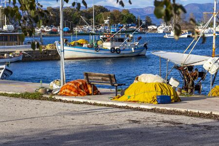 Stray dog sleeping on a pile of fishing nets at the Fanari Port, fishing boats in the background. At Fanari, Rhodope prefecture, Greece Stok Fotoğraf