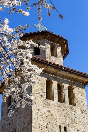Batkunski Monastery of Sts Peter and Paul at the village of Patalenitsa, Pazardzhik Province, Bulgaria. Bell tower behind blurred blooming spring tree branches Stock fotó