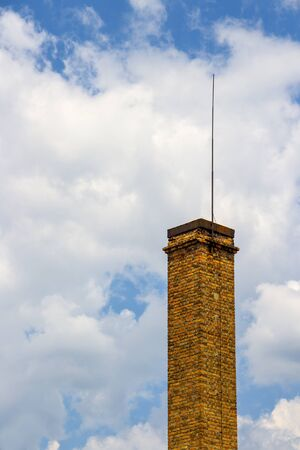 High brick chimney of the old public bath in Kazanlak, Stara Zagora Province, Bulgaria on a sunny summer day against the cloudy sky Foto de archivo