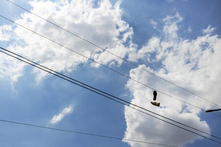 Pair of old sneakers hanging by the laces from a power line against the cloudy sky. Shoe dangling in Kazanlak, Stara Zagora Province, Bulgaria