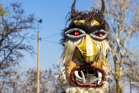 Horned male kuker mask at the National Festival Dervishi Varvara 2019, village of Varvara, Pazardzhik Province, Rhodope Mountains, Bulgaria