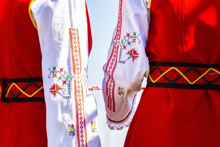 Rear partial view of national garbs on two unidentified Bulgarian young women at the National Festival Dervishi Varvara 2019, village of Varvara, Pazardzhik Province, Rhodope Mountains Stock Photo