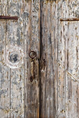 Old wooden weathered door with a rusty latch in Fano, Province of Pesaro and Urbino, Marche Region, Italy