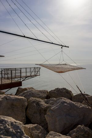Shore-operated lift net at the Port of Senigallia, Province of Ancona, Marche Region, Italy, glittering Adriatic Sea water surface in the background, Chinese fishing net